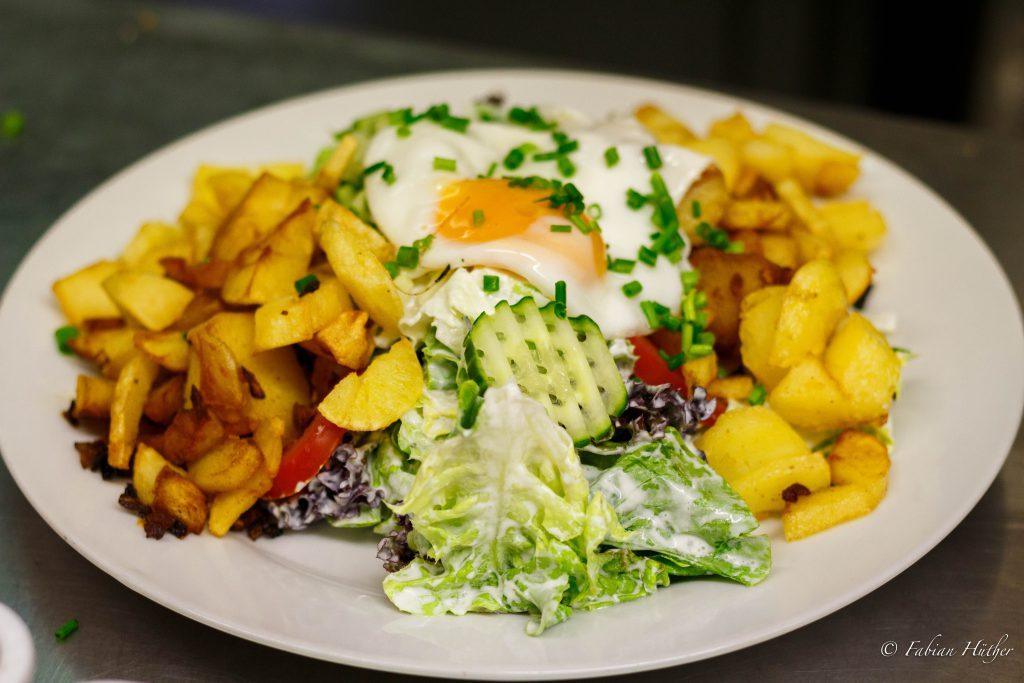 Kornhaussalat Salate der Saison, T omate, Gurke dazu Bratkartoffeln und Spiegelei